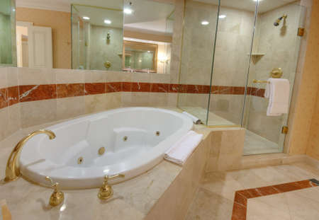 White jacuzzi bathtub and brass taps decorated with marble tiles