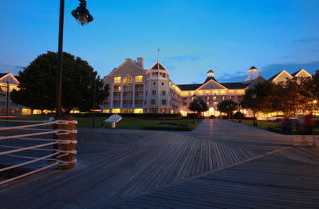 Illuminated resort and wooden boardwalk at night