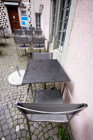 Wet metallic tables and chairs in rainy day at pavement cafe photo