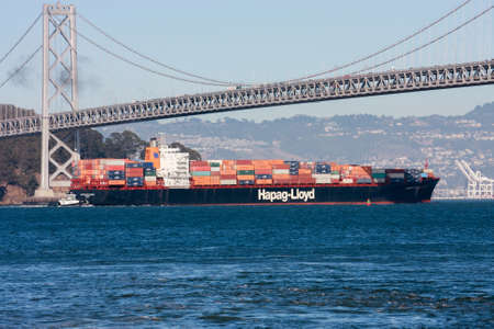 containership: SAN FRANCISCO, US - SEPT 20, 2010: Hapag-Lloyd container ship moving under  Oakland Bay Bridge on its way to the Port of Oakland in San Francisco on Sept 20, 2010.