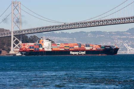 oakland: SAN FRANCISCO, US - SEPT 20, 2010: Hapag-Lloyd container ship moving under  Oakland Bay Bridge on its way to the Port of Oakland in San Francisco on Sept 20, 2010.