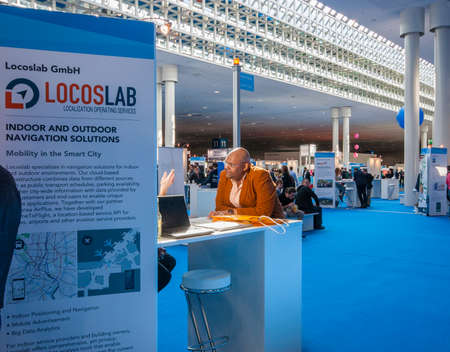 attendee: HANNOVER, GERMANY - MARCH 14, 2016: Attendee visits stand of Locoslab company  at CeBIT information technology trade show in Hannover, Germany on March 14, 2016.