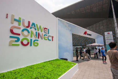 the world expo: SHANGHAI, CHINA - SEPTEMBER 2, 2016: Attendees of Huawei Connect 2016 IT conference near entrance to World Expo Exhibition and Convention Center in Shanghai, China on September 2, 2016.