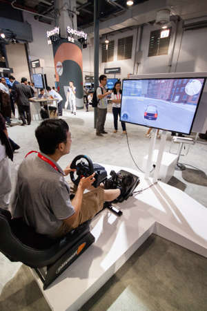 attendee: SHANGHAI, CHINA - SEPTEMBER 2, 2016: Attendee of Huawei Connect 2016 information technology conference test auto training simulator at exhibition hall in Shanghai, China on September 2, 2016. Editorial