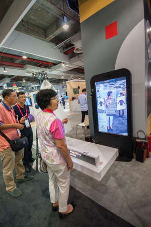 fitting in: SHANGHAI, CHINA - SEPTEMBER 2, 2016: Attendees of Huawei Connect 2016 information technology conference test virtual fitting room simulator at exhibition hall in Shanghai, China on September 2, 2016.