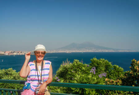 Happy mature tourist woman travelling in Italy with video camera on her neck on the Naples bay and Vesuvius mountain background.