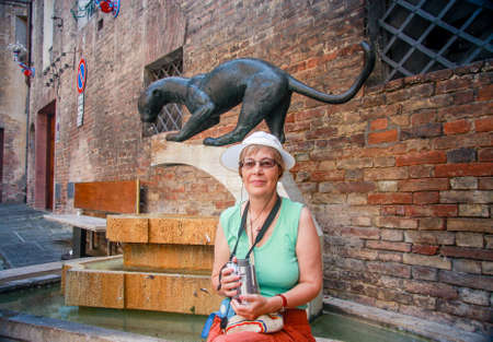 Mature tourist woman travelling in Siena, Tuscany, Italy with video camera on her neck sitting at fountain with monument of panther that symbolize one of 17 Siena districts.