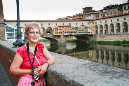 Mature tourist woman travelling in Italy with video camera on her neck stays against Ponte Vecchio bridge in Florence.