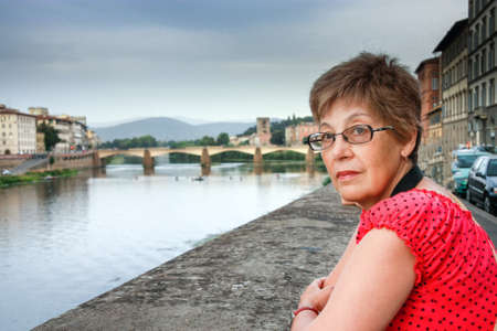 Mature tourist woman travelling in Italy stays against bridge over Arno river in Florence.