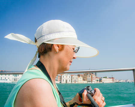 Mature tourist woman travelling in Italy sails on boat in Venice and shoots video.