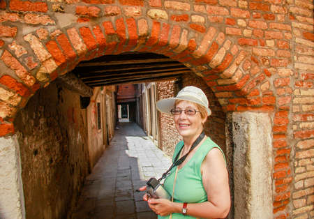 Happy mature tourist woman travelling in Italy stays against narrow street and arch in Venice.  Stock Photo