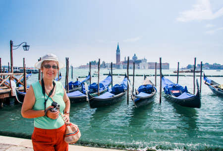 Mature tourist woman travelling in Italy stays against row of gondolas moored by Saint Mark square against San Giorgio di Maggiore church in Venice.