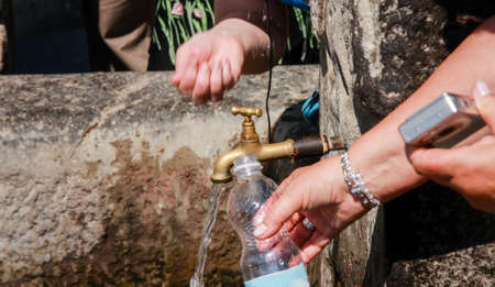 Tourists fill plastic bottle with fresh water from obsolete brass tap in stone wall