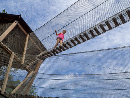 MOSCOW, RUSSIA - JULY 26, 2018: Unidentified girl goes on extreme rope ladder  way with safety net in childrens amusement park Lukomorye in Moscow, Russia on July 26, 2018. Editorial