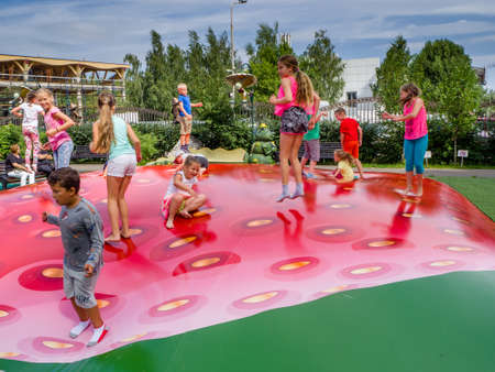 MOSCOW, RUSSIA - JULY 26, 2018: Unidentified joyful children are jumping fun on inflatable trampoline in form of strawberry in childrens amusement park Lukomorye in Moscow, Russia on July 26, 2018. Editorial