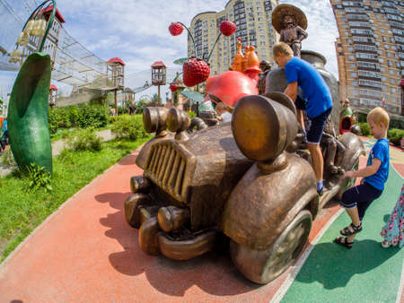 MOSCOW, RUSSIA - JULY 26, 2018: Unidentified boys play with car playground equipment in childrens amusement park Lukomorye in Moscow, Russia on July 26, 2018.