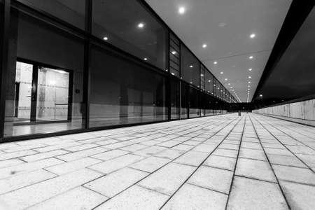 Perspective lumineuse de passage piéton le long de la façade en verre de bâtiment la nuit