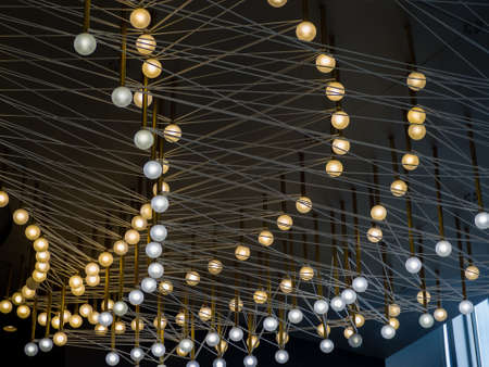 Modern lighting interior decoration with ball-shaped colored lighting bulbs suspended under black ceiling on stretched cables  Stok Fotoğraf