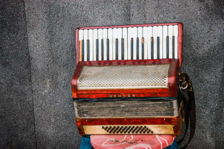 NAPLES, ITALY - SEPT 9, 2008: Old Hohner accordion left by a street musician on a stool in Naples, Italy on Sept 9, 2008.