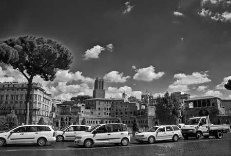 Row of white cars on Rome cobblestone pavement Stock Photo