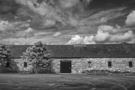 One-storeyed old-fashioned stone traditional warehouse against cloudscape sky Stock Photo