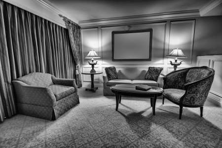 Classic sitting room with sofa, armchair, table and lamps Stock Photo