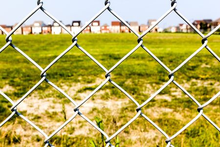 Chain link fence against a green grass and houses in the background  photo