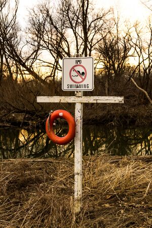 No swimming sign on white board and cross.