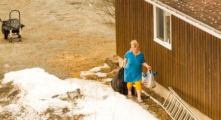 美しい女性の春の大掃除に大きなゴミ袋を運ぶします。 写真素材