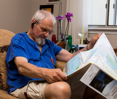 individualist: Siting senior man with glasses reading a map.