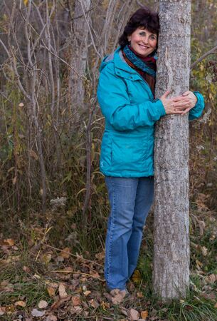 Happy woman hugging a tree in the forest.