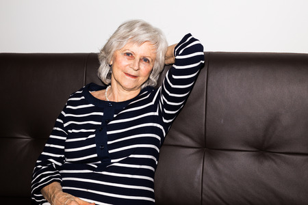 80s adult: A  senior woman showing that she enjoys retirement by relaxing.