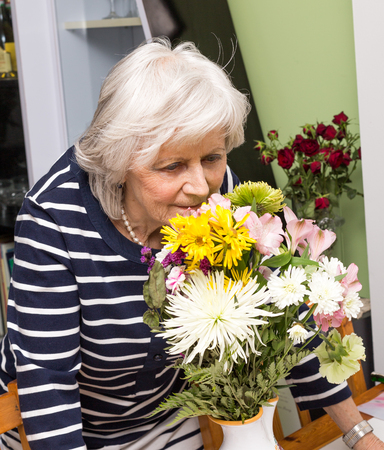 80s adult: Woman showing that she enjoys retirement by relaxing and smelling flowers. Stock Photo