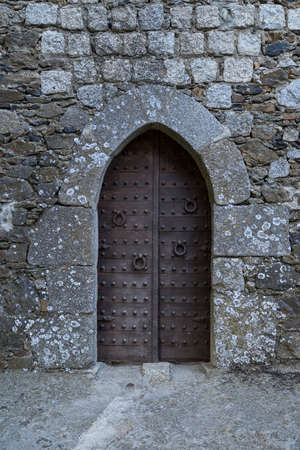 Ancient iron gates of a medieval castle with knockers and rustic studs Editorial
