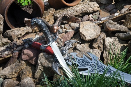 stab: Photo of cold steel against the background of natural stones. Stock Photo
