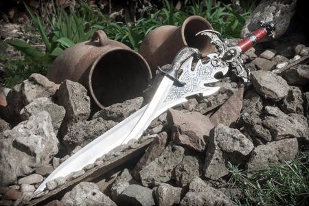 scheide: Foto von kaltem Stahl vor dem Hintergrund von Natursteinen. Lizenzfreie Bilder