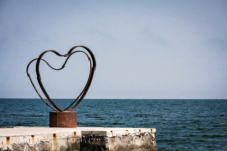 Iron heart on the dock in the sea.