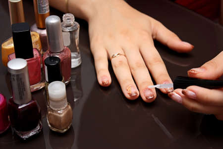 A woman make a manicure  There are a lot of bottles with a varnish on a table  photo