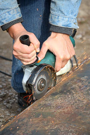 A worker cuts a metal by grinding wheel  photo