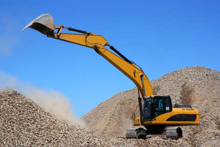 Dredge loads a rubble against the blue sky