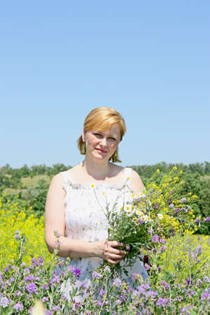 The adult pretty woman with a bunch of flowers photo