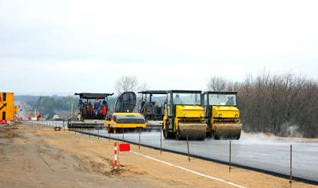 construction crew: Road crew operate automatic asphalt spreader and steam roller follows