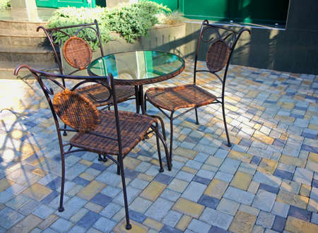 Table and chairs in a patio before an entrance to the building