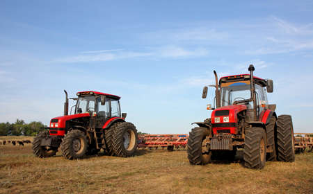 harrow: Color photo of two red tractors with a harrow