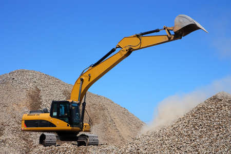 Dredge loads a rubble against the blue sky photo