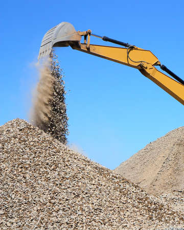 Rubble spilling out of the bucket dredge on background of blue sky photo