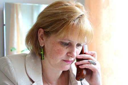 Adult serious business woman in the office call by phone