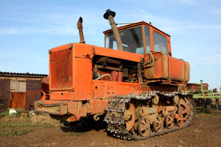 Crawler tractor with a plow on the background of rural buildings photo