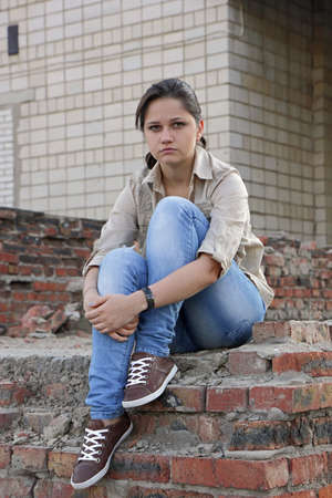 resentful: Resentful young woman sitting on the destroyed wall of the building
