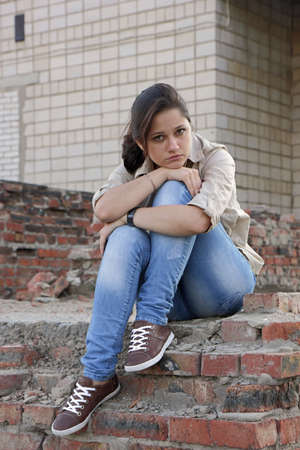 ordeal: Wailful young woman sitting on the destroyed wall of the building